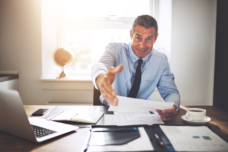 Smiling mature businessman reaching out for a handshake while sitting at his desk in an office holding paperwork Foto de archivo