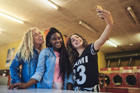 Smiling young female friends standing in a laundry place taking a selfie while doing laundry together Banco de Imagens
