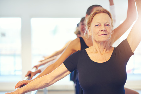 Smiling aged woman looking at camera while dancing ballet with group in the class.