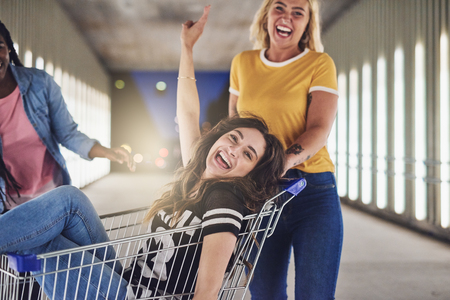 Laughing young woman sitting in a shopping cart being pushed down a walkway in the city by two girlfriends