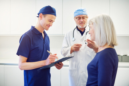 Adult doctor consulting mature woman while young assistant standing and writing in tablet.