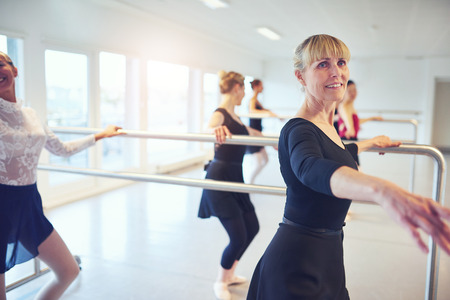 Group of female dancers standing and practicing in ballet class. Banque d'images
