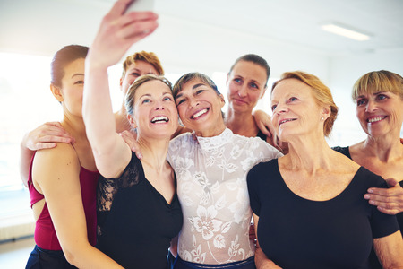 Mixed age group of laughing women standing arm in arm together taking a selfie during ballet class