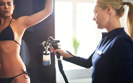 Kosmetiker, der Aerograph verwendet und Bodypaint Tan zur jungen hübschen weiblichen Hüfte im Schönheitssalon sprüht.