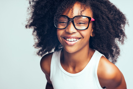 Smiling young African girl with long curly hair wearing glasses while standing by herself against a gray background Stock Photo