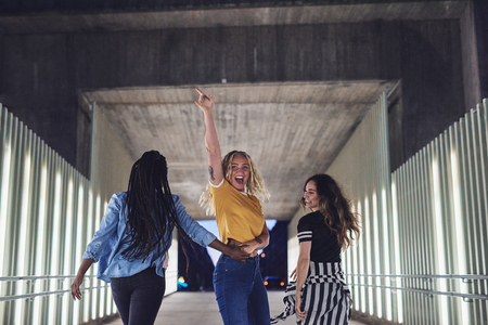 Laughing group of diverse young girlfriends having fun while walking together down a walkway in the city at night