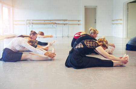 Side view of unrecognizable women dancing ballet sitting on floor and bending while doing gymnastics in the class.