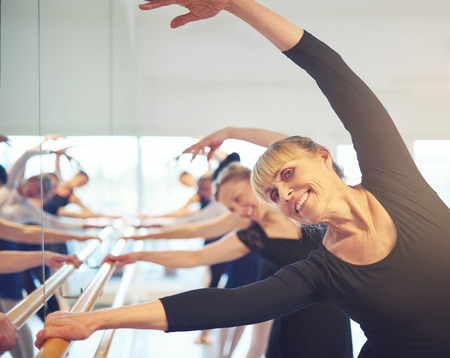 Cheerful adult women standing and stretching with hands up in ballet class. Stock Photo - 93046338