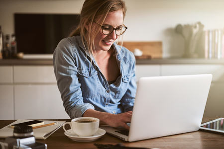Smiling young woman working on her small business with a laptop while sitting at her kitchen table at home