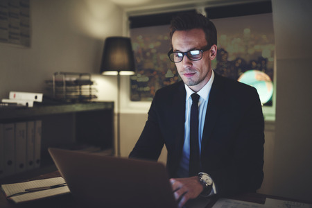 businessman typing while sitting at the laptop in the office at night. Stock Photo