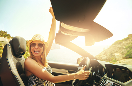 Young pretty cheerful woman in hat and sunglasses driving cabriolet and holding one hand up in excitement.  Banco de Imagens