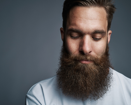 Closeup of a serious young man with a long beard wearing a t shirt deep in thought while standing against a gray background