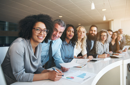 Porträt einer lächelnden Gruppe von verschiedenen Firmen Kollegen , die in einer Reihe zusammen an einem Tisch in einem hellen modernen Büro stehen
