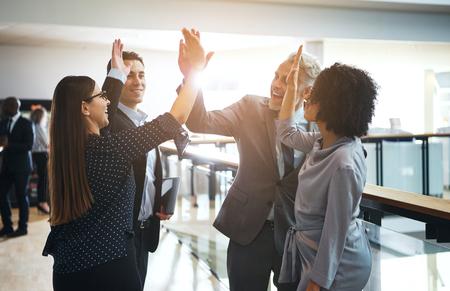 Zróżnicowana grupa uśmiechniętych biznesmenów przybijająca sobie piątkę stojąc razem w korytarzu nowoczesnego biurowca