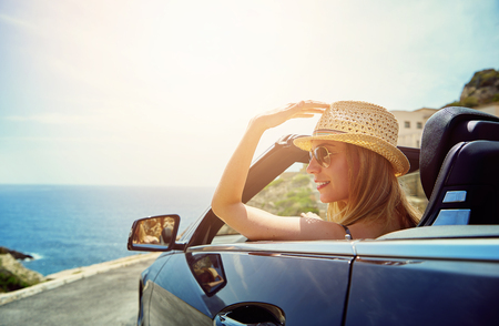 Young blonde sitting in cabriolet and looking away on blue sea in sunlight.  Imagens