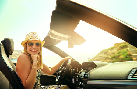 Young pretty female in summer hat and glasses sitting in cabriolet and making gesture of excitement.