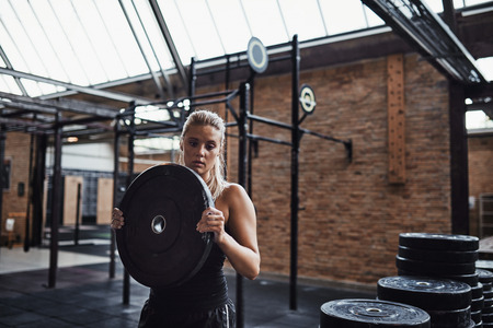 Fit young blonde woman in sportswear selecting weights for a workout session while standing alone in a gym