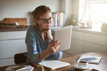 Focused young female entrepreneur working online with a digital tablet while sitting at her kitchen table at home