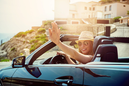 Young female in sunglasses sitting in cabriolet and waving with hand at camera on background of seaside.  Imagens