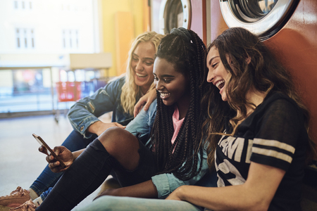 Group of smiling young girlfriends sitting on a laundry barfloor using a cellphone together while doing laundry