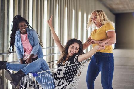 2人の女性の友人によって街の歩道にショッピングカートに押されながら笑う若い女性 写真素材