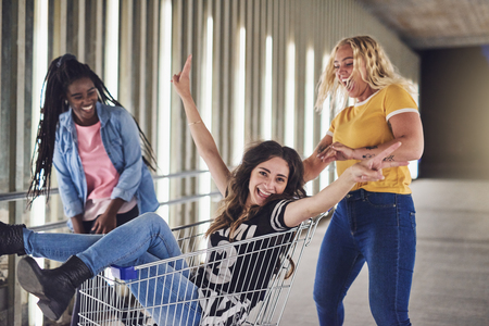 Young woman laughing while being pushed in a shopping cart down a walkway in the city by two female friends