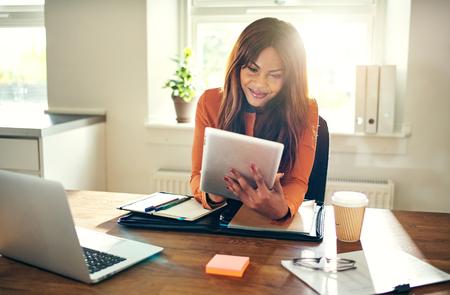 Lächelnder junger afrikanischer weiblicher Unternehmer , der online mit einer digitalen Tablette beim Sitzen an einem Schreibtisch in ihrem Innenministerium arbeitet Standard-Bild
