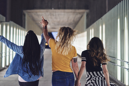 Rearview of a group of diverse young girlfriends holding hands while walking together down a walkway in the city at night
