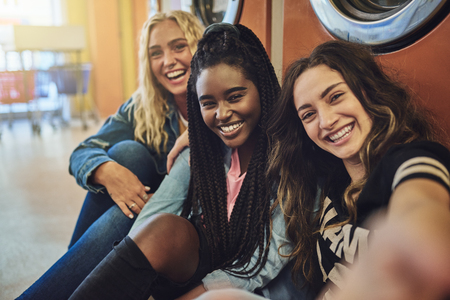Group of smiling young female friends sitting on a  floor taking selfies while doing laundry together