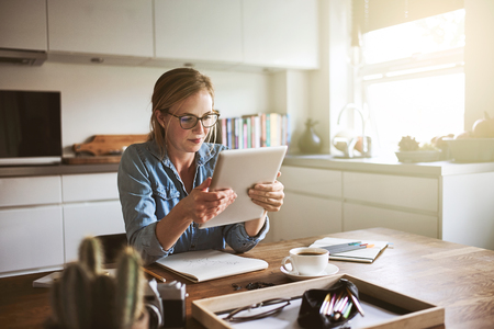 Young woman sitting at her kitchen table at home working on her small business with a digital tablet Standard-Bild