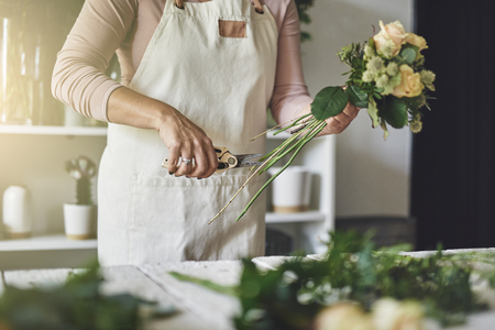 Young woman working at a table in her flower shop trimming the stems of flowers while making a bouquet