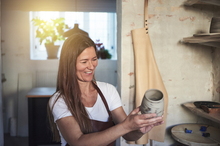 Female artisan standing alone in her creative ceramic workshop inspecting a newly crafted piece of pottery Stockfoto