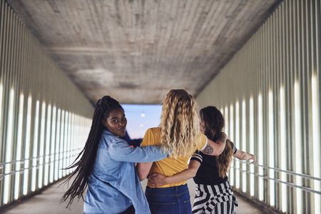 Rearview of a group of young girlfriends having fun while walking arm in arm together down a walkway in the city at night