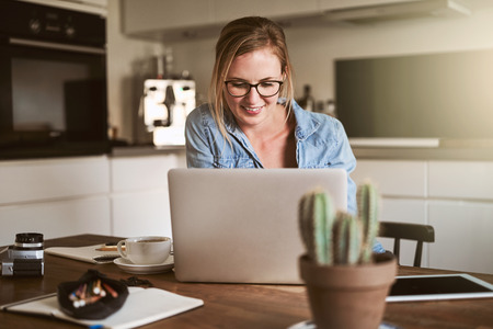 Young female entrepreneur smiling while sitting in her kitchen a home working online with a laptop Foto de archivo