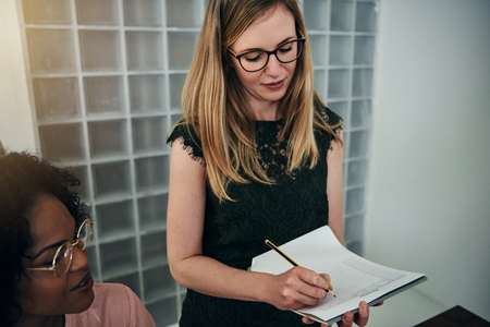 Smiling businesswoman writing down notes on a clipboard while working with a colleague in a modern office