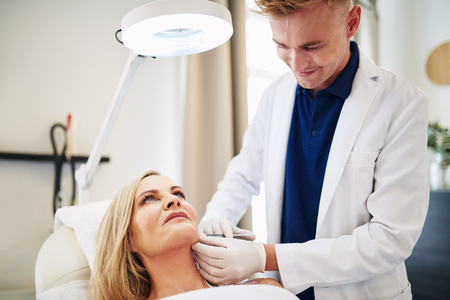 Young male doctor focused on performing a injection to the chin of a mature woman lying on a table in a beauty clinic Фото со стока