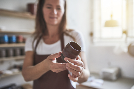 Smiling female artisan standing alone in her creative workshop examining a newly made piece of glazed pottery Stock fotó