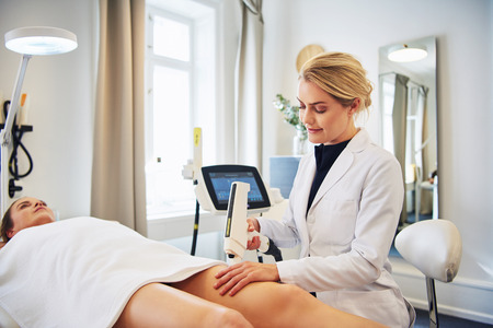 Young female technician performing a laser hair removal procedure on the legs of a young woman lying on a table in a beauty clinic