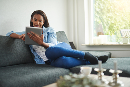 Young African woman relaxing the sofa in her living room at home browsing online with a digital tablet 스톡 콘텐츠