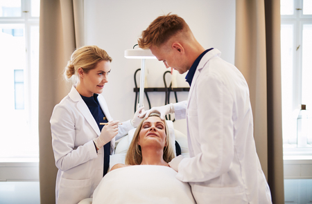 Two doctors planning a cosmetic surgery procedure on the face of a mature woman lying with her eyes closed on a table in a clinic Stock Photo