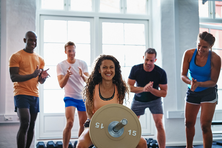 Smiling young woman straining to lift a barbell with friends cheering her on in the background while enjoying a workout at the gym 스톡 콘텐츠
