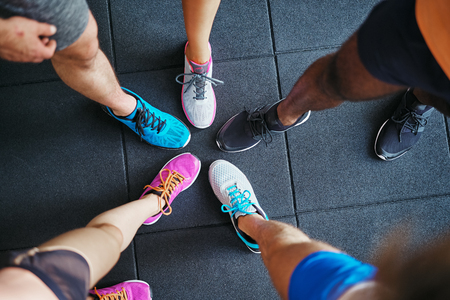 High angle of a group of sporty peoples feet wearing running shoes standing together in a huddle on a gym floor