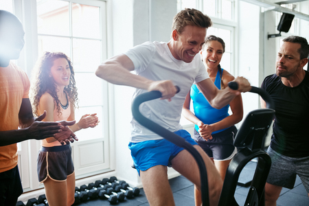 Group of cheering people encouraging their friend riding a stationary bike while working out together in a gym Stock Photo