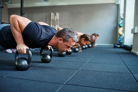Focused group of people working out together on the floor with weights during a health club class Standard-Bild - 92984361