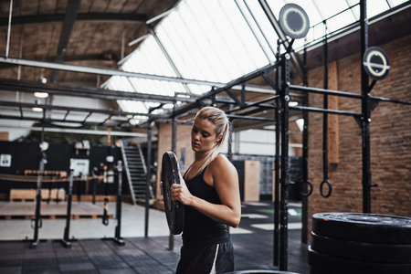 Young blonde woman in sportswear selecting weights for a workout session while standing alone in a gym