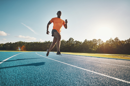 Focused young African runner in sportswear racing alone down a running track on a sunny day Stock Photo