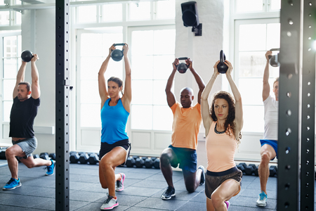 Diverse group of young people doing lunges with weights in a gym together during a workout Stock fotó