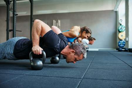 Focused group of people working out together on the floor with weights during a health club class