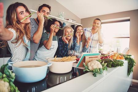 Amigos que llevan tallos de espárragos debajo de la nariz mientras están parados frente a una mesa llena de ollas, fideos y verduras Foto de archivo
