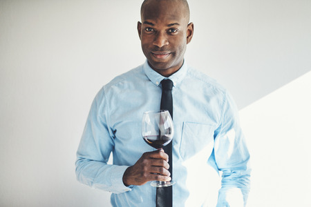 Sophisticated mature African man in a shirt and tie drinking a glass of red wine